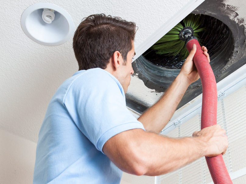 Man cleaning an air duct